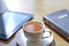Vicino ad una tazza la compressa e le bugie della bibbia Fotografie Stock Libere da Diritti