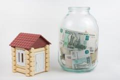 Vicino alla casa è la banca del giocattolo con le banconote delle rubli russe di denominazioni differenti Immagine Stock Libera da Diritti