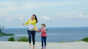 Vicino alla madre ed alla figlia della spiaggia che giocano negli uccelli video d archivio