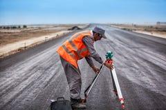 Vicino a Bajkonur, il Kazakistan - 10 giugno 2011, lavoratore della strada sulla costruzione della strada Immagine Stock Libera da Diritti