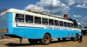 Vicino a Chengi, lo Zambia: Uomini che cambiano pneumatico di riserva del bus di viaggio immagini stock libere da diritti