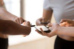 Vicino della gente consumi gli smartphones che scambiano i contatti immagini stock