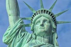 Vicino della statua della libertà su isolato nel fondo nuvoloso blu Fotografia Stock Libera da Diritti
