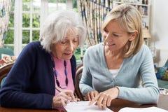 Vicino femminile che aiuta donna senior a completare formulario Fotografia Stock Libera da Diritti