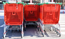 vicino su dei carrelli metallici e di plastica rossi riordinati in parecchie file che aspettano essere utilizzato dai compratori  immagini stock libere da diritti