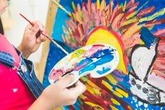Vicino su della mano della ragazza dipinga un'immagine la ragazza nel gruppo di studente prescolare si è seduta il disegno un'imm fotografia stock