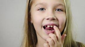 Vicino - su della ragazza sorridente sveglia, zanna scuotente del latte del dito del bambino all'interno con fondo bianco Perdita video d archivio