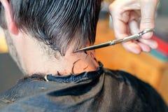 Vicino su delle mani del parrucchiere che tagliano mèche dei capelli dell'uomo Occupazione professionale del barbiere o del parru fotografia stock