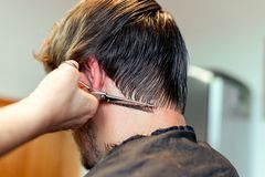 Vicino su delle mani del parrucchiere che tagliano mèche dei capelli dell'uomo Occupazione professionale del barbiere o del parru immagine stock