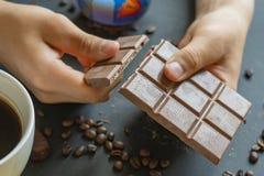 Vicino su due mani fendi una barra di cioccolato con la tazza di caffè f fotografie stock