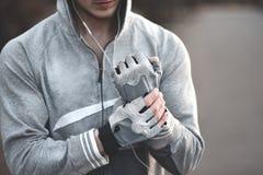 Vicino su, il tipo di sport mette i guanti sulle sue mani prima della preparazione fotografia stock