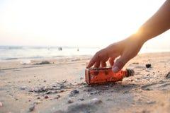 Vicino su raccolga a mano la bottiglia di vetro sulla spiaggia fotografie stock libere da diritti