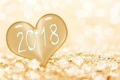 2018, vicino su su un cuore del ghiaccio alla luce dorata del bokeh della neve immagini stock