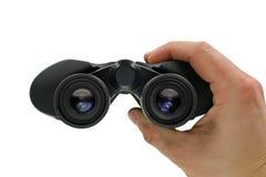 Vicino su, vista frontale della mano che tiene il binocolo nero su fondo bianco fotografie stock