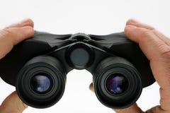 Vicino su, vista frontale delle mani che tengono il binocolo nero su fondo bianco immagine stock
