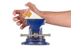 Vicios - mano que ase para los cigarrillos sostenidos en un apretón del tornillo fotografía de archivo libre de regalías