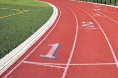Vicoli di una pista di corsa rossa con i numeri Fotografia Stock Libera da Diritti