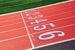 Vicoli di una pista di corsa rossa con i numeri Fotografie Stock Libere da Diritti