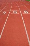 Vicoli di una pista di corsa rossa con i numeri. Fotografia Stock Libera da Diritti