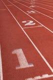 Vicoli su una pista corrente atletica con il numero Immagini Stock Libere da Diritti