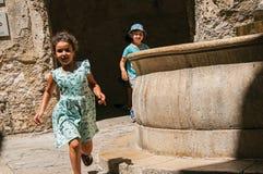 Vicolo con gli arché, i bambini e la fontana di pietra in San-Paul-de-Vence immagini stock libere da diritti