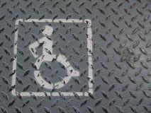 Vicolo del segno di handicap della sedia a rotelle sul fondo grigio del metallo Fotografia Stock