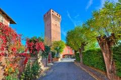 Vicolo e torre medievale alta rossa in Piemonte, Italia. Immagine Stock