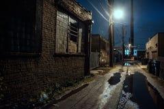 Vicolo industriale scuro, granuloso e bagnato della città alla notte immagine stock