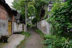 Vicolo non pavimentato ombreggiato fra le case antiche cinesi nel gre di estate Immagine Stock Libera da Diritti