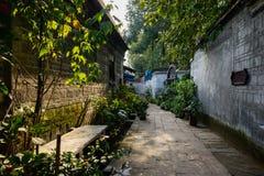 Vicolo ombreggiato fra il muro di mattoni e le case invecchiate nell'inverno soleggiato a Fotografia Stock Libera da Diritti