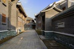 Vicolo ombreggiato fra le costruzioni tradizionali archaised in poppiero soleggiato Fotografia Stock Libera da Diritti