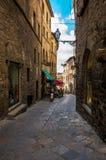 Vicolo stretto facente un giro turistico nel vecchio centro urbano di Voltera, Italia immagine stock
