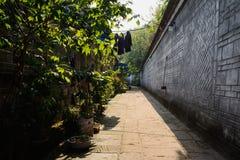 Vicolo stretto fra la parete e le case invecchiate nell'inverno soleggiato aftern Immagine Stock