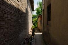 Vicolo stretto protetto fra le vecchie costruzioni dell'abitazione nel riassunto soleggiato Fotografie Stock