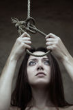 Victim. Sad lady holding the slipknot of the scaffold Royalty Free Stock Images