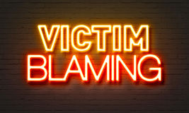 Victim blaming neon sign on brick wall background. Stock Image