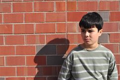 Victim of bullying. A boy is looking with a very sad face, looking for help. He is a victim of bullying royalty free stock photo