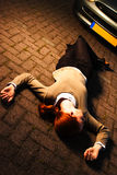 Victim of a Car Accident. A supposedly dead or injured woman laying on the ground after she has been hit by a car in an accident at night Stock Photos