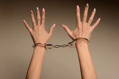 Victim of fashion. The concept. Beautiful female hands with manicure in handcuffs.  Royalty Free Stock Images