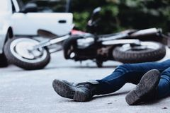 Victim of motorbike accident. Victim of a motorbike accident lying on the street unconscious Royalty Free Stock Photos
