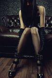 Victim. Gothic girl with legs in leg cuffs royalty free stock photo