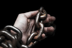 Victim, slave, prosoner male hands tied by big metal chain by hi Royalty Free Stock Photo
