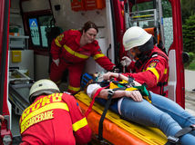 Victim on stretcher. Transported by firefighters to the ambulance. Paramedic closing security straps Stock Image