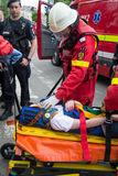 Victim on stretcher. Young woman on stretcher transported by firefighter to the ambulance. Paramedic holding oxygen mask on victim face Royalty Free Stock Image
