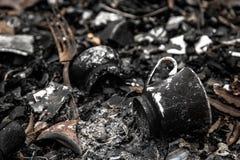 Victims of fire. Ash, trash, fork, burned coffee pot, closeup, sad memento royalty free stock photo