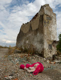 Victims of war. Little doll lying in front of a destroyed building, inside a war zone stock image