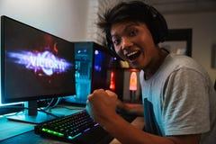 Victoire asiatique enthousiaste de réjouissance de garçon de gamer tout en jouant la vidéo g image stock