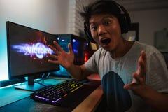 Victoire asiatique gaie de réjouissance de garçon de gamer tout en jouant la vidéo g photographie stock