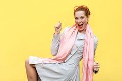 Victoire ! Réjouissance de femme de gingembre pour son succès D'isolement sur le jaune image stock