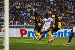 Victor Moses. SHAH ALAM - JULY 21: Chelsea Football Club player Victor Moses (white jersey) attempts to shoot past Mohd Fadhli (27) and Amiridzwan Tajudin (6) in Stock Image